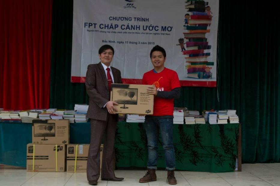"""Đại diện Viện Đào tạo Liên kết quốc tế trao tặng Tủ sách """"FPT Chắp cánh ước mơ"""" cho ông Phùng Ngọc – Hiệu trưởng Trường THCS Bình Định (Bắc Ninh)."""